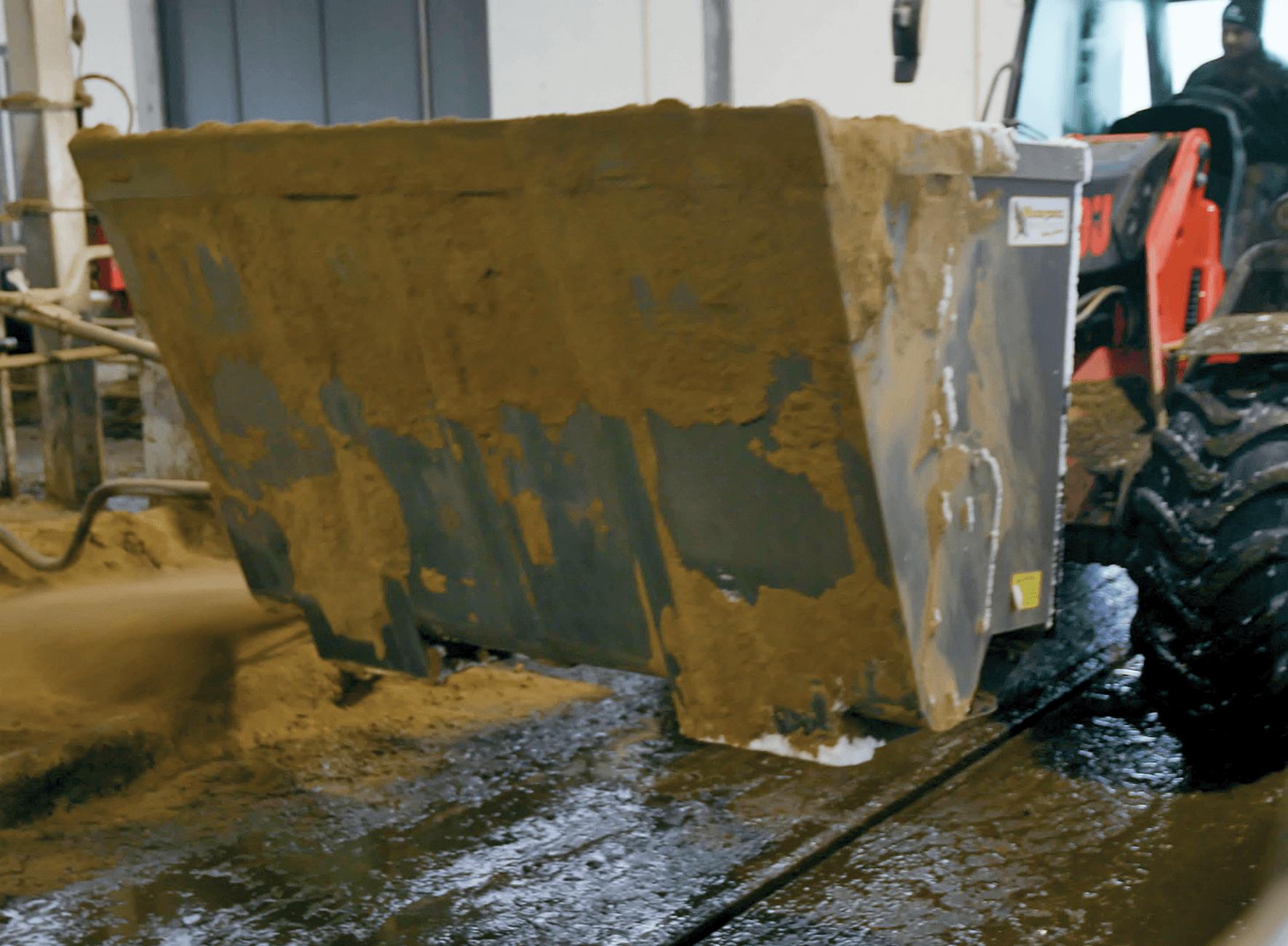 Kurottajalla ja hiekanlevityskauhalla hiekoitetaan makuuparsia pihattonavetassa